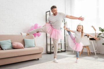 Vader en dochter doen samen aan ballet in de woonkamer