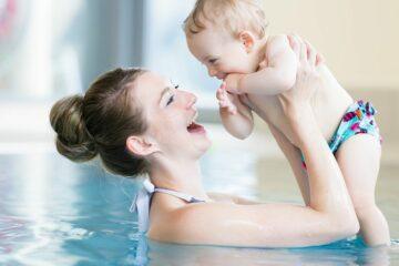 Moeder kletst met baby in het zwembad