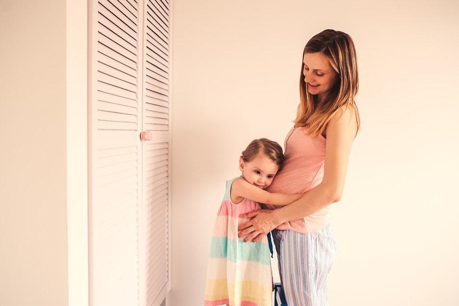 Peuter knuffelt de buik van haar zwangere moeder