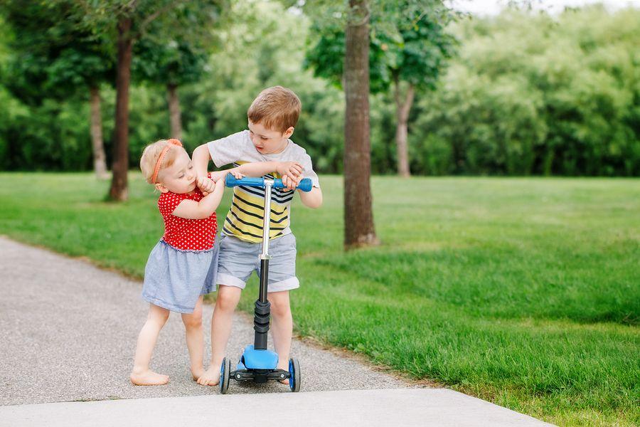 Peuter vertoont agressief gedrag tegen haar broer in ruzie om step