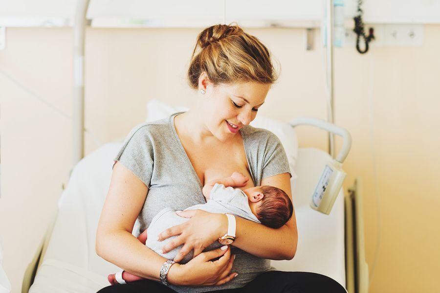 Vrouw houdt haar pasgeboren baby vast na poliklinische bevalling