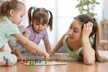 Moeder en peuters spelen bordspelletje