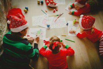 Vader ligt tijdens feestdagen met kinderen kerstknutsels te maken,