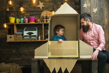 Vader en peuter hebben samen een raket gebouwd van een kartonnen doos om als speelgoed voor een peuter van 3 jaar te dienen