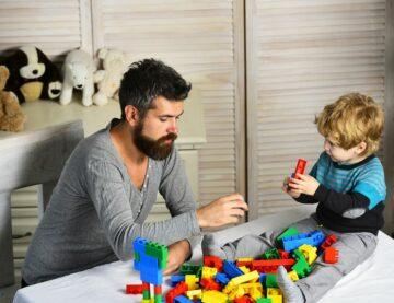 Vader en peuter spelen samen met lego