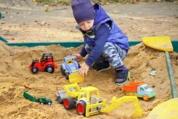 Peuter speelt met zijn speelgoed in de zandbak