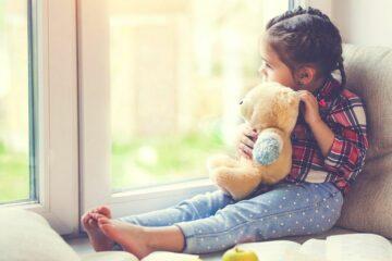 Peutermeisje kijkt verdrietig naar buiten na het scheiden van haar ouders