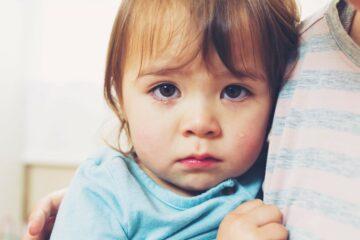Verdrietig meisje wordt getroost door ouder na scheiden van haar ouders