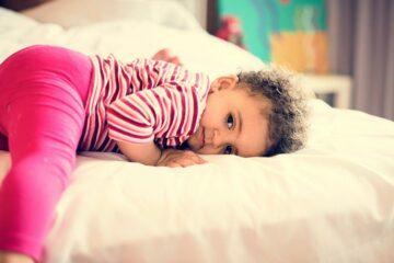 Verlegen peuter ligt op bed