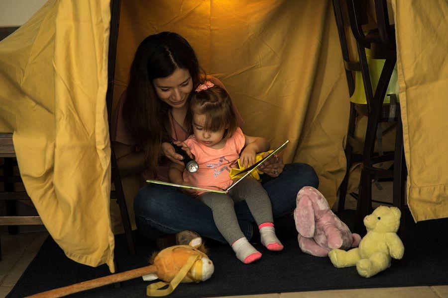 Peuter en moeder zitten samen in zelfgebouwde hut van stoelen en lakens