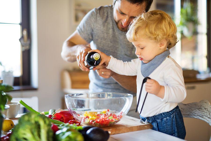 Peuter van 2 jaar helpt vader met koken