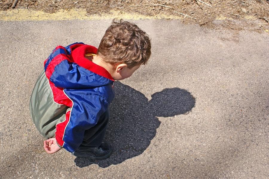Kind van 2 jaar kijkt naar eigen schaduw