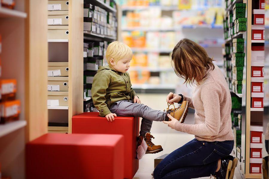 Peuter past nieuwe kinderschoenen in de winkel