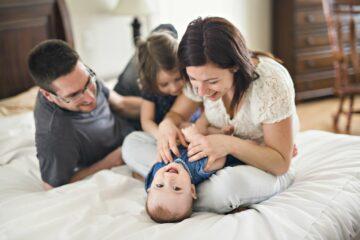Ouders knuffelen met hun twee kinderen op bed, wat past bij positief opvoeden