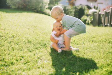 Peuter heeft voldoende sociaal-emotionele ontwikkeling doorgemaakt om te snappen dat zijn zusje blij wordt van een kus