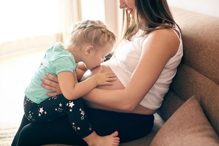 Peuter van 3 jaar oud kust zwangere buik van moeder