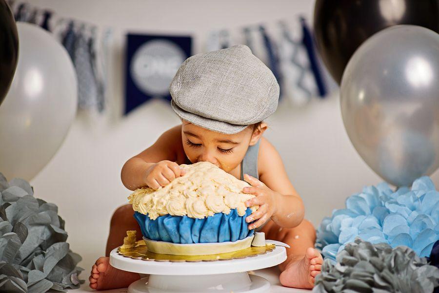 Baby eet een smash cake met zijn vingers