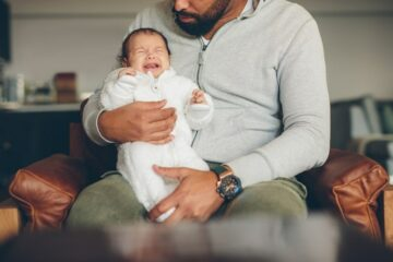 Baby huilt met eerste tranen en zit bij vader op schoot