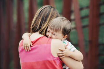 moeder troost peuter na val en past wondzorg toe