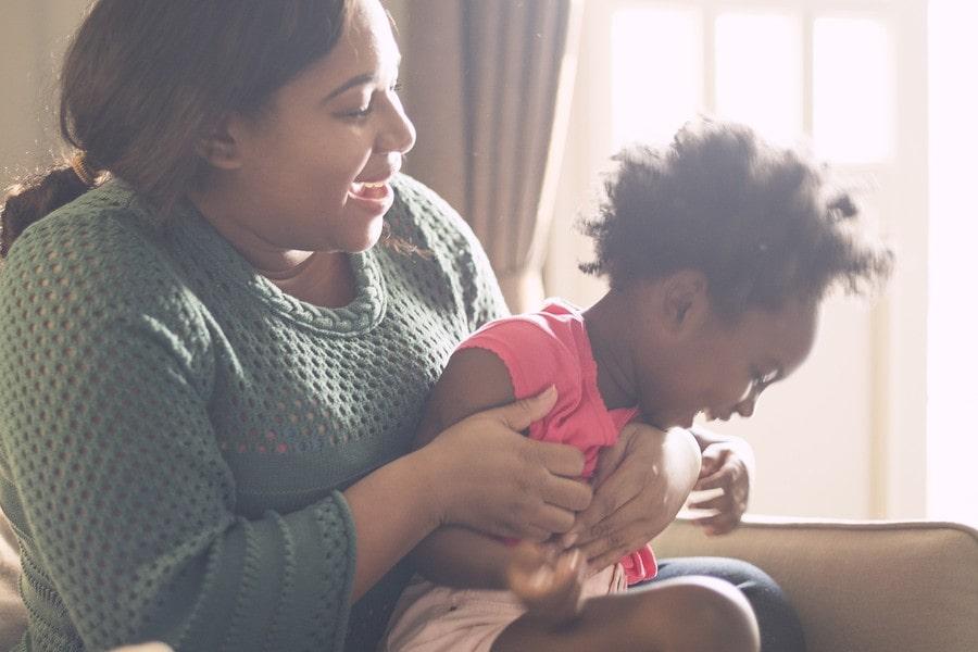 2e62e81f7c407f Kind van 2,5 jaar zit lachend bij moeder op schoot