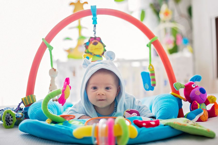 Baby speelt met babyspeelgoed op speelkleed