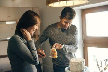 Aanstaande vader en moeder snijden gender reveal taart aan