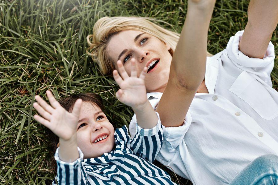 Hoogsensitief kind ligt samen met zijn moeder in het gras