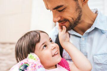 peuter kijkt heimelijk lachend naar vader terwijl ze aan het liegen is
