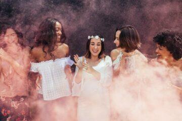 Vrouwen op een gender reveal party met roze rook