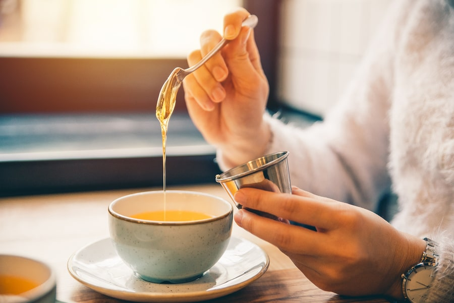 Zwangere vrouw doet honing in haar thee tijdens de zwangerschap