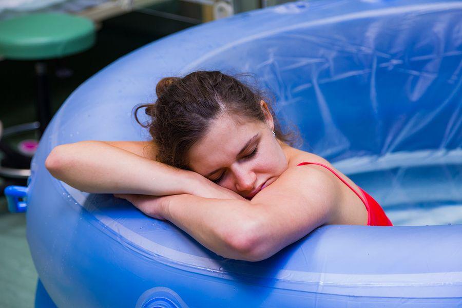 Vrouw met ontsluiting bevalt in bad