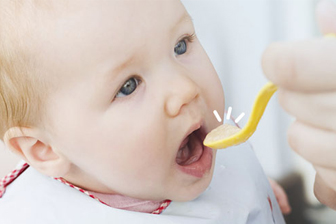 baby eet tussendoortje met gele lepel