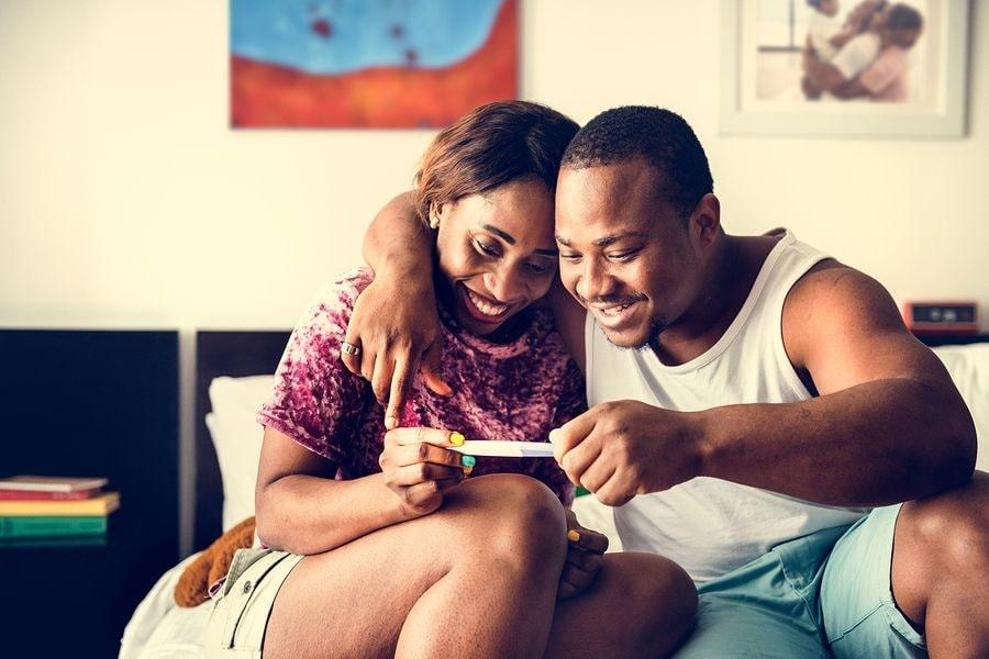 Man en vrouw bekijken positieve zwangerschapstest bij 1 maand zwanger