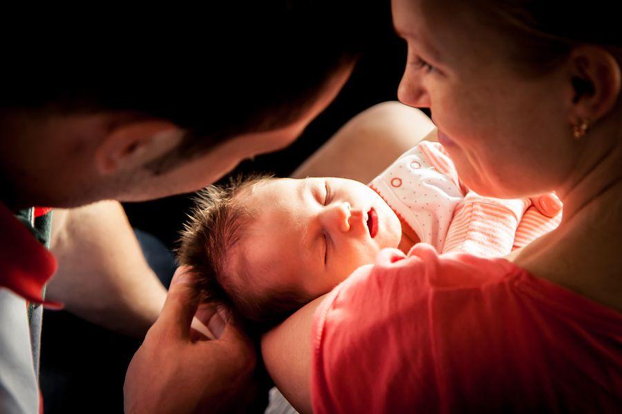 Vader en moeder met pasgeboren baby vlak na de bevalling