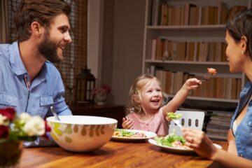 Peuter zit met ouders aan tafel en leert op speelse wijze tafelmanieren