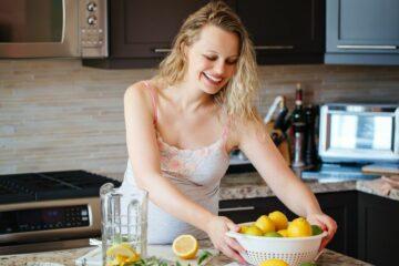Zwangere vrouw snijdt citroenen om de juiste zwangerschapsvitamines binnen te krijgen