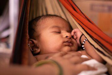 Baby slaapt in hangmat bij hitte, waar slaaptips van pas komen