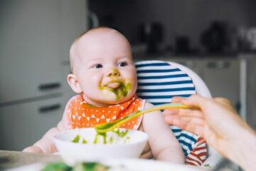 Baby eet spinaziehapje om voldoende vitamines binnen te krijgen