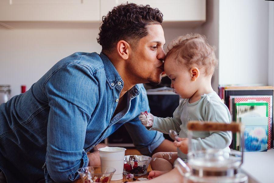 Vader en baby eten samen blauwe bessen, waarbij risico op verstikking bestaat