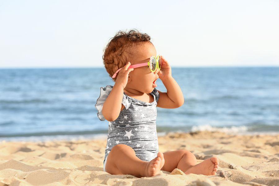Kindje zit op het strand en draagt een babyzonnebril