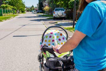 Moeder wandelt met hydrofiele doek over kinderwagen, wat gevaarlijk is