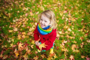 Meisje geniet van spelen in de natuur met herfstblaadjes