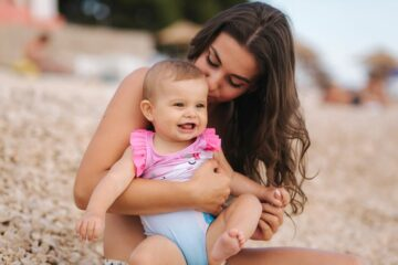 Moeder en baby op het strand moeten oppassen voor warmte uitslag