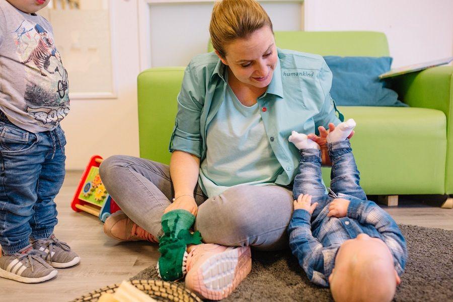 Begeleidster van het kinderdagverblijf speelt met kindje