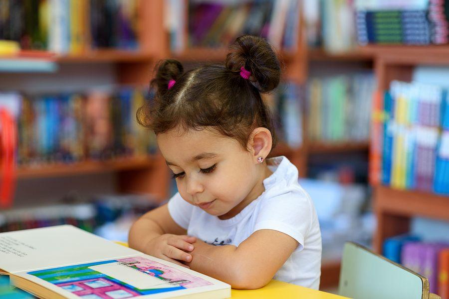 Meisje leest een boekje op het kinderdagverblijf