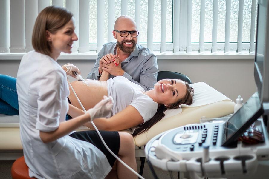 Zwangere vrouw krijgt echo en haar partner kijkt mee