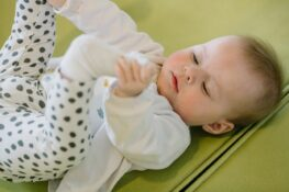 Baby speelt met voetjes op kinderopvang