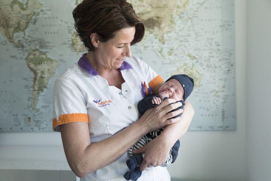 Kraamzorg houdt baby vast op haar arm
