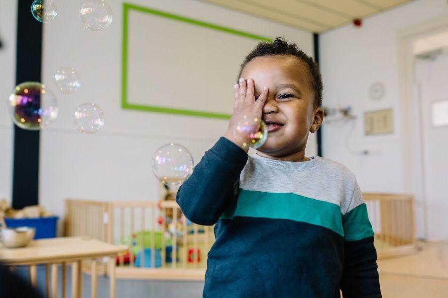 Jongetje speelt op de kinderopvang nadat de kosten kinderopvang zijn voldaan
