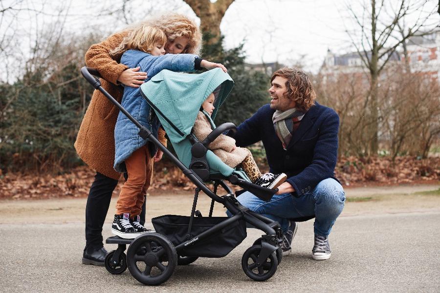 Jong gezin is met twee kinderen op pad met de kinderwagen accessoire